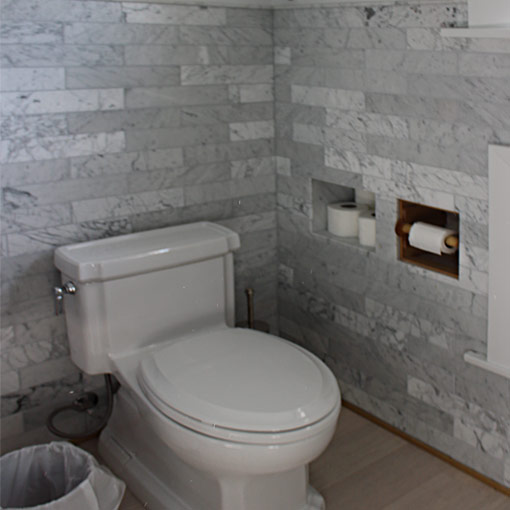 Bathroom-remodel-Carrara-marble-tile-walls-commode-by-Ceramic-Finishes,-Los-Angeles