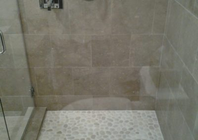 Contemporary-shower-with-river-rock-floor-base-by-tile-contractor-Ceramic-Finishes
